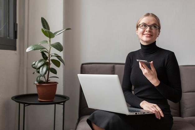 Mulher no sofá com celular e laptop