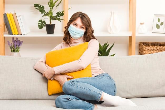 Mulher no sofá com máscara