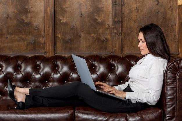Mulher no sofá com o laptop