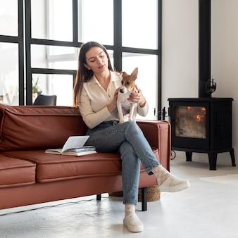 Mulher no sofá com seu cachorro no colo