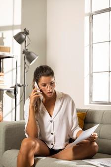 Mulher no sofá falando ao telefone e olhando para o papel
