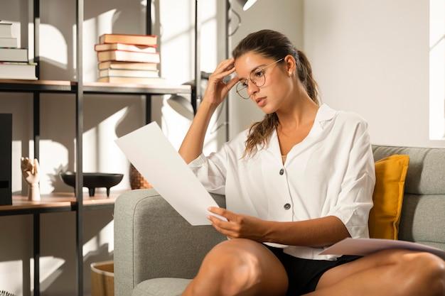 Mulher no sofá olhando para o papel
