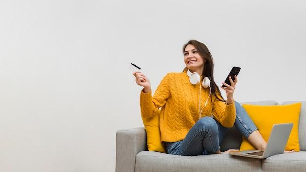 Mulher no sofá, segurando o smartphone em uma mão e um cartão de crédito na outra