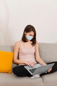 Mulher no sofá usando laptop