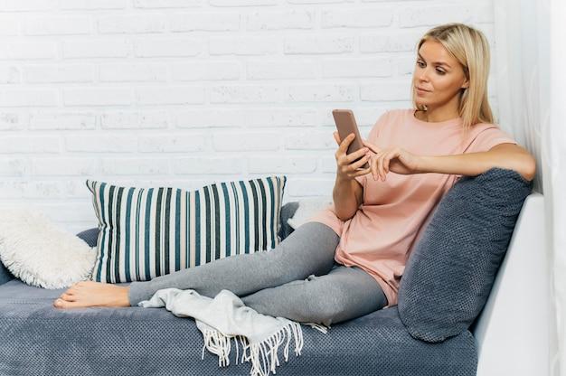 Mulher no sofá usando smartphone em casa durante a pandemia