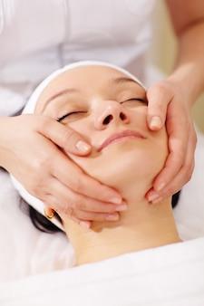 Mulher no spa de beleza recebendo uma massagem facial