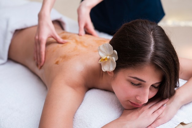 Mulher no spa, desfrutando de uma massagem nas costas