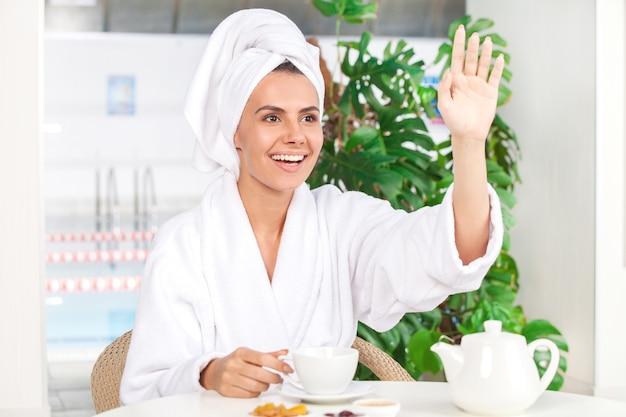 Mulher no spa. mulher jovem e atraente em roupão de banho bebendo chá e gesticulando enquanto está sentada em frente à piscina