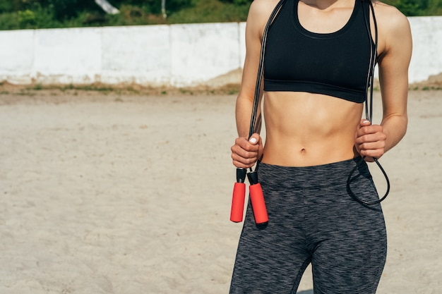 Mulher no sportswear com uma corda de pular nas mãos na praia de manhã