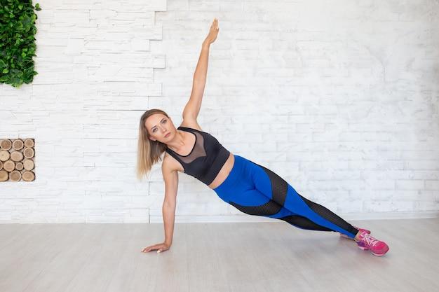 Mulher no sportswear da moda fazendo exercícios de fitness ioga