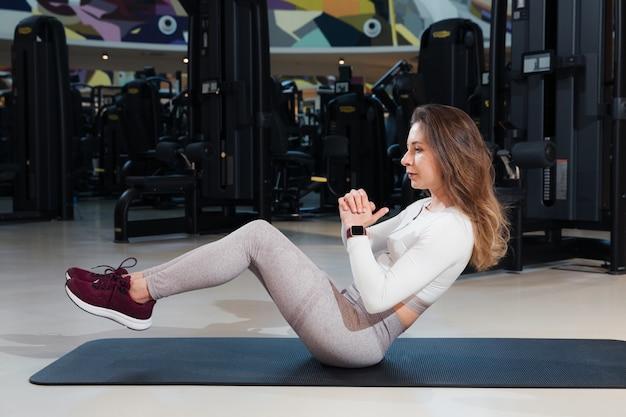 Mulher no sportswear está treinando na academia