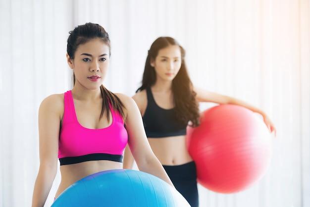 Mulher no sportswear prática yoga treino alongamento no ginásio interior.