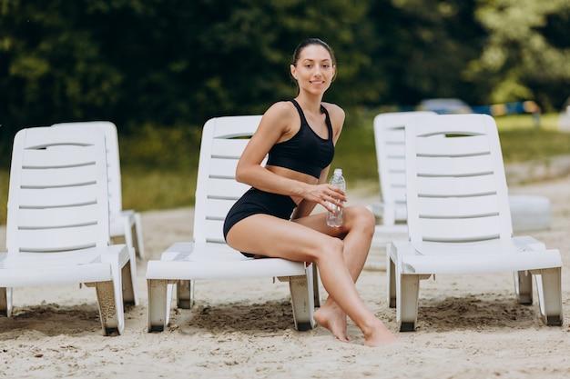 Mulher no sportswear, sentado na cadeira de praia na praia, segurando uma garrafa com água