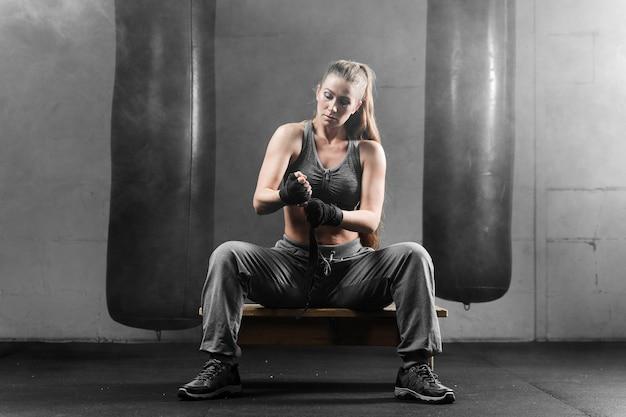Mulher no sportswear, sentado no banco e se preparando para o treinamento