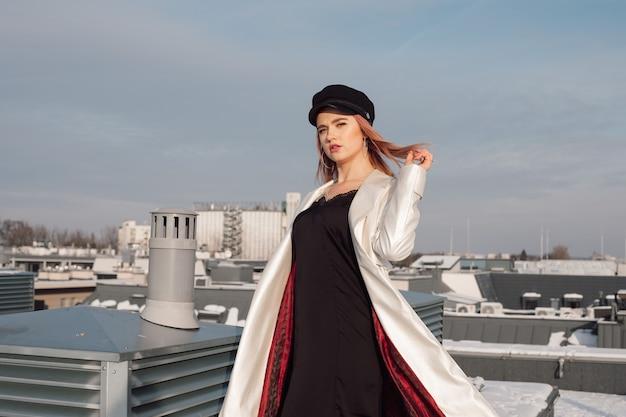 Mulher no telhado do edifício contra o céu azul em raios de sol frio de inverno. ela está usando um vestido preto deslizante, capa branca com forro e boné vermelhos. mantendo o cabelo ruivo ao vento