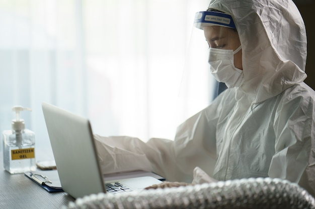 Mulher no trabalhador protetor do terno do hazmat no computador do laboratório que analisa no laboratório. parar de espalhar o coronavírus ou o covid-19.