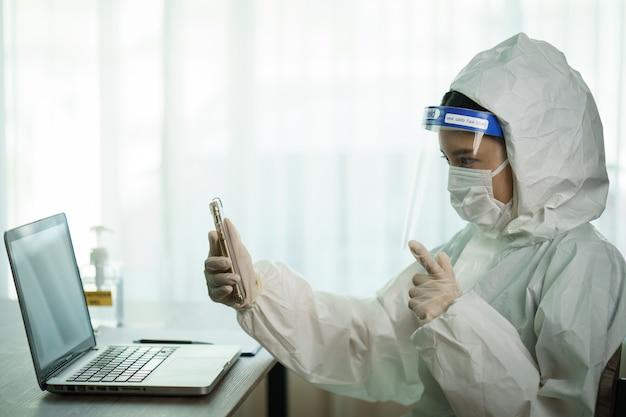 Mulher no trabalhador protetor do terno do hazmat no descanso do computador de laboratório e vídeo chamando no telefone esperto. parar de espalhar o coronavírus ou o covid-19.