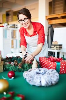 Mulher no trabalho, fazendo uma guirlanda de natal e embrulhando presentes
