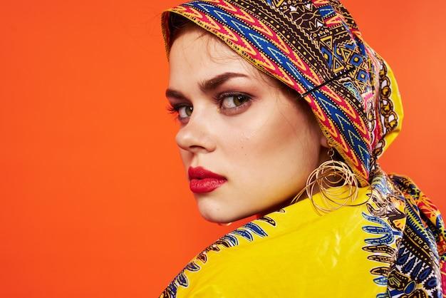 Mulher no turbante multicolorido lábios vermelhos atraente parece parede isolada.
