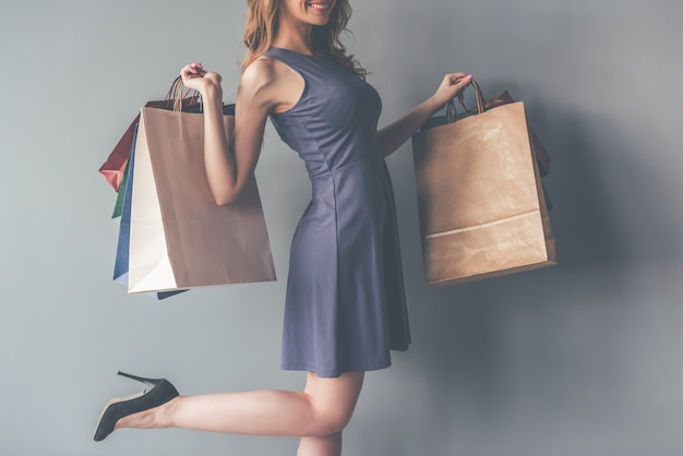 Mulher no vestido de cocktail que guarda sacos de compras.
