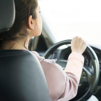Mulher no volante por cima da vista do ombro