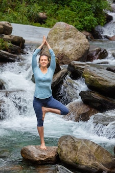 Mulher no yoga asana vrikshasana árvore pose na cachoeira ao ar livre