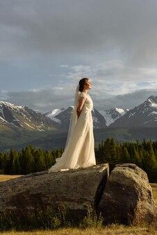 Mulher noiva em pé com os olhos fechados em uma pedra na montanha e apreciando o pôr do sol