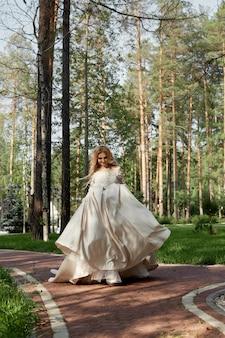 Mulher noiva em um luxuoso vestido de noiva fofo corre ao longo do caminho para o casamento