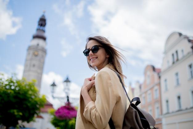 Mulher nos óculos de sol e na trouxa no quadrado envelhecido do centro de cidade. polônia