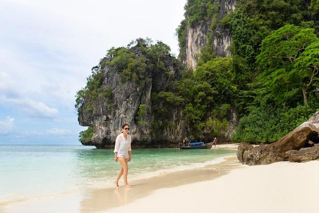 Mulher nos óculos de sol que anda na praia do mar em férias de verão.