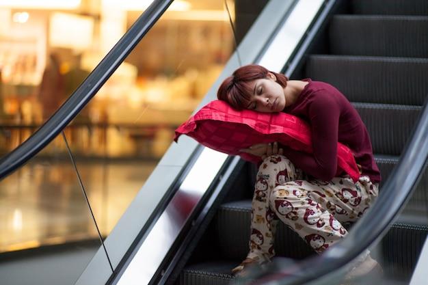 Mulher nos pijamas para dormir em uma escada rolante