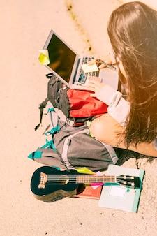 Mulher, notas levando, com, calculadora, ligado, laptop, em, dia ensolarado