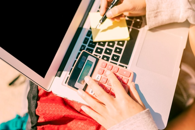 Mulher, notas levando, ligado, laptop, em, dia ensolarado
