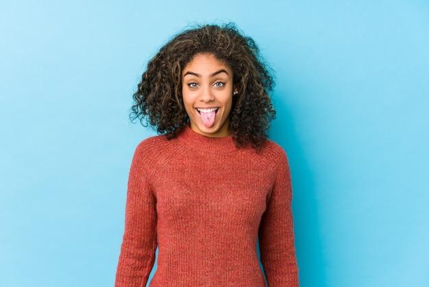 Mulher nova afro-americano do cabelo encaracolado engraçada e amigável saindo da língua.