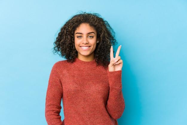 Mulher nova afro-americano do cabelo encaracolado que mostra o número dois com dedos.