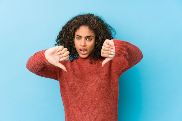Mulher nova afro-americano do cabelo encaracolado que mostra o polegar para baixo e que expressa a antipatia.