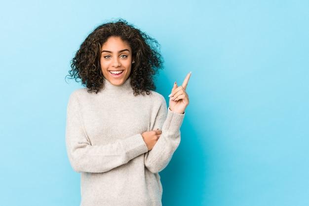 Mulher nova afro-americano do cabelo encaracolado que sorri alegremente apontando com o dedo indicador afastado.