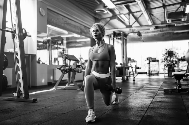 Mulher nova atlética da aptidão que exercita na ginástica