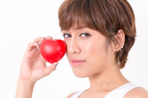 Mulher nova bonita de ásia com coração vermelho. conceito para saudável.