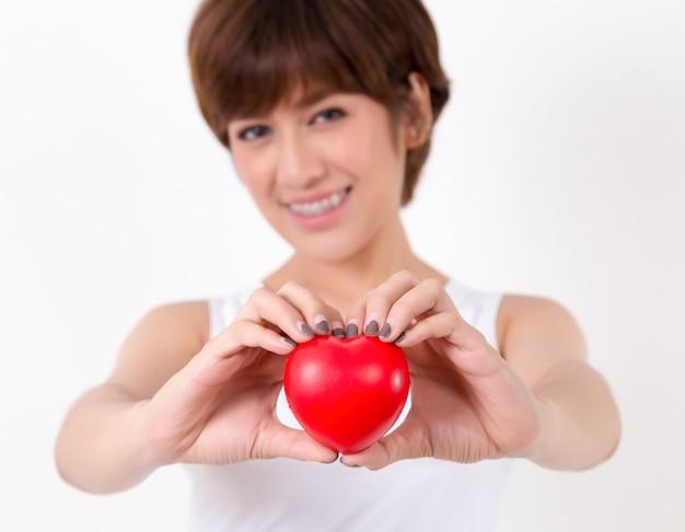 Mulher nova bonita de ásia com coração vermelho. isolado no fundo branco