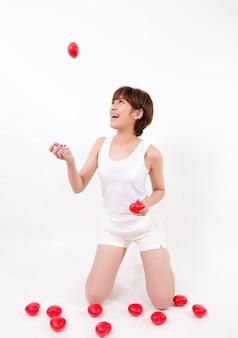 Mulher nova bonita de ásia com corações vermelhos. isolado no fundo branco.