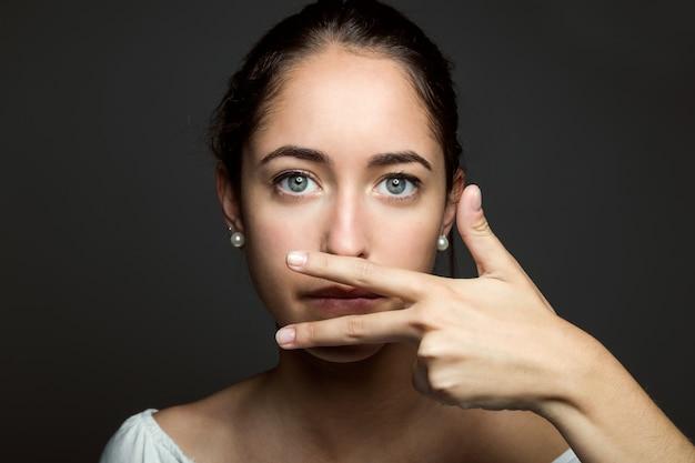 Mulher nova bonita que cobre sua boca com mão. isolado.