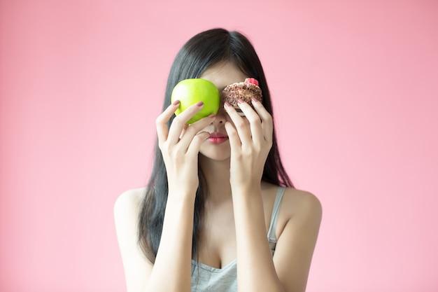 Mulher nova bonita que faz uma escolha entre um bolo e uma maçã