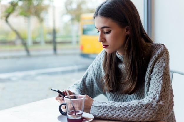 Mulher nova bonita que usa seu telefone móvel no café.