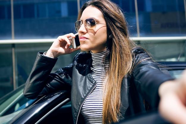 Mulher nova bonita que usa seu telefone móvel no carro.
