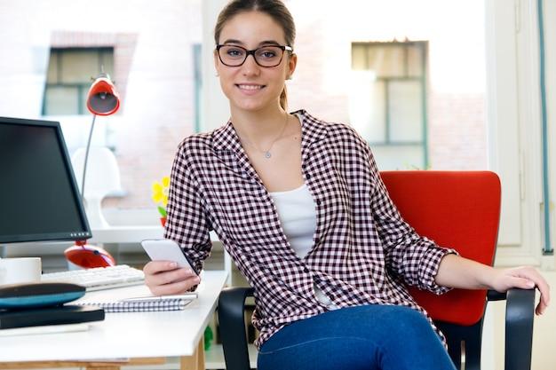 Mulher nova bonita que usa seu telefone móvel no escritório.