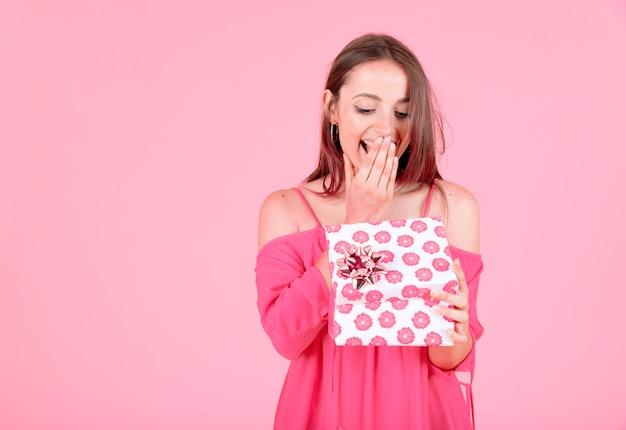 Mulher nova chocada que abre a caixa atual floral com curva contra o fundo cor-de-rosa