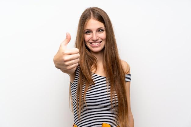 Mulher nova com cabelo longo sobre a parede branca isolada com polegares acima porque algo bom aconteceu