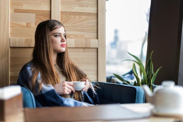Mulher nova com copo de café olhando pela janela