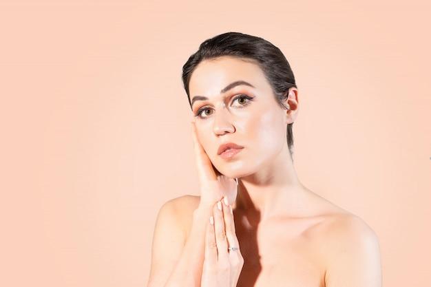 Mulher nova com pele desobstruída que toca em suas mãos sua face.
